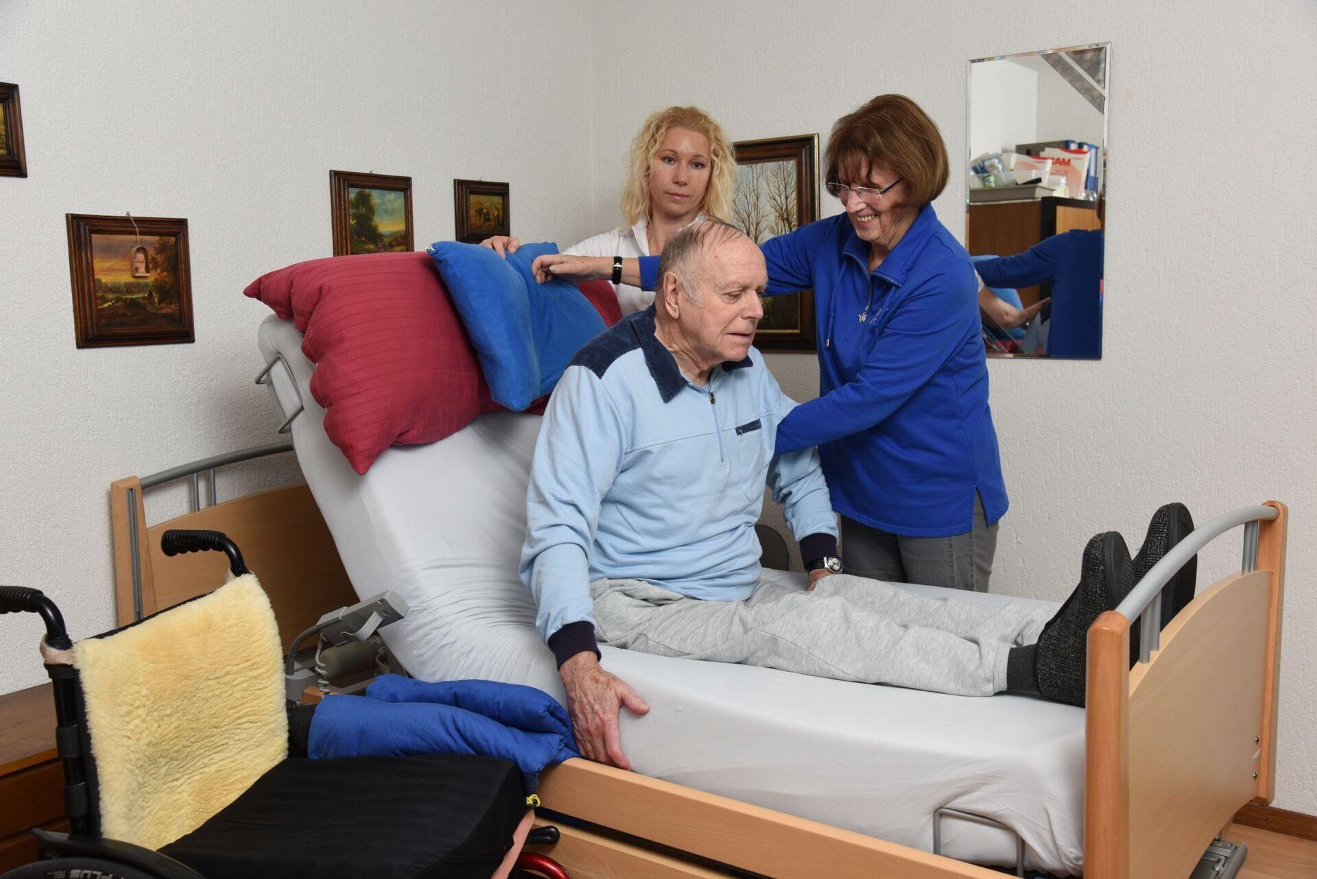 Zwei Pflegerinnen an einem Bett mit einem Patienten